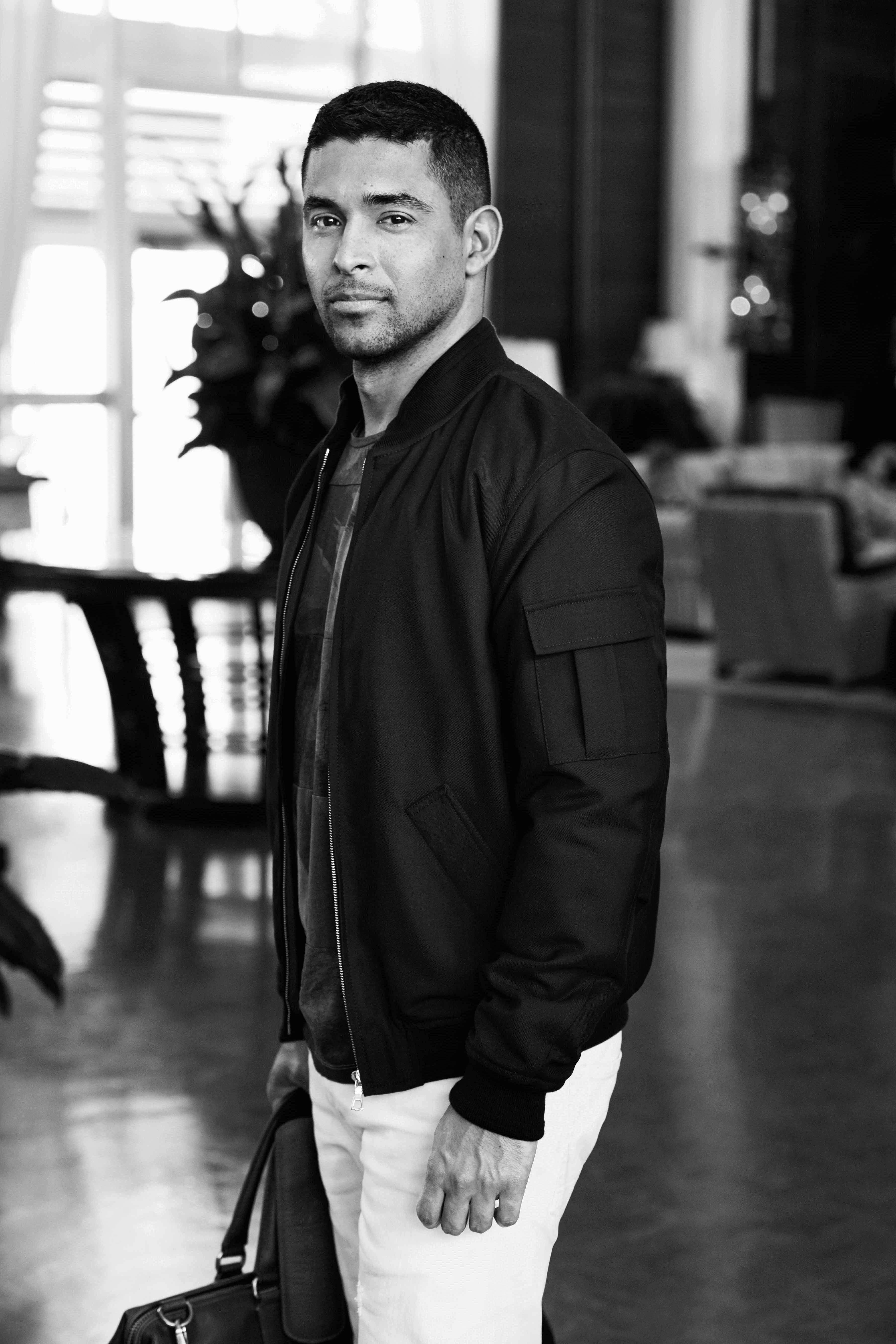 A black and white photo of Wilmer Valderrama with his body turned to the left but looking straight ahead and wearing white pants and a bomber jacket