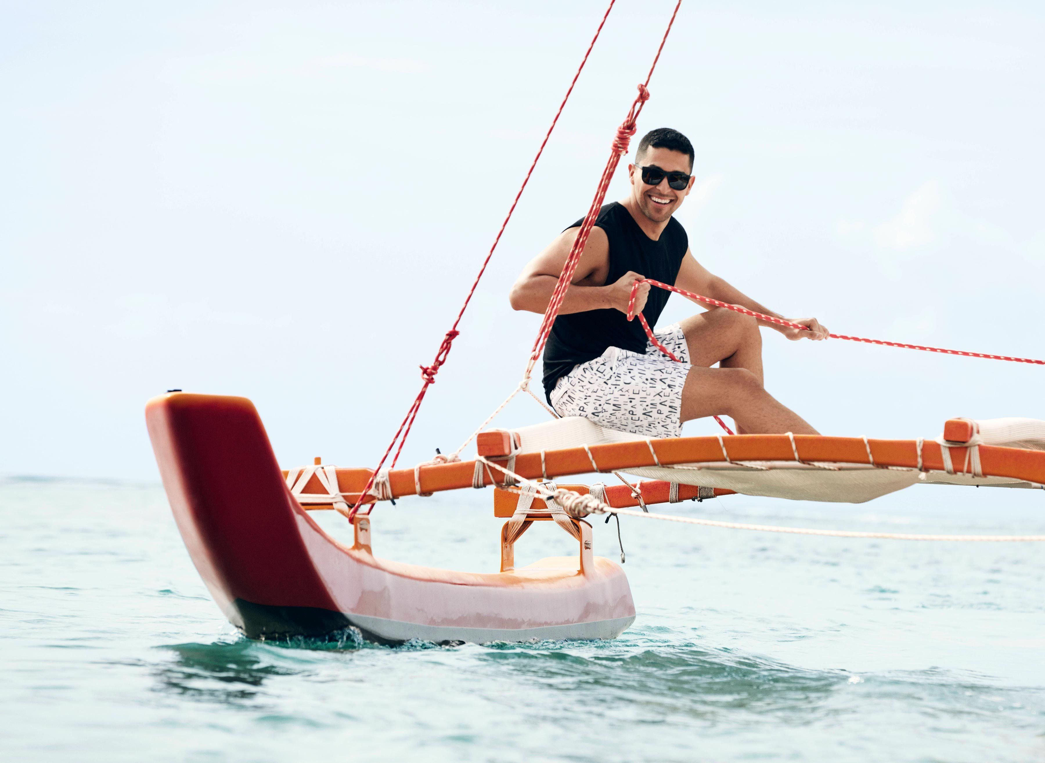 Wilmer Valderrama sailing on the ocean in a black tank top and white swim trunks