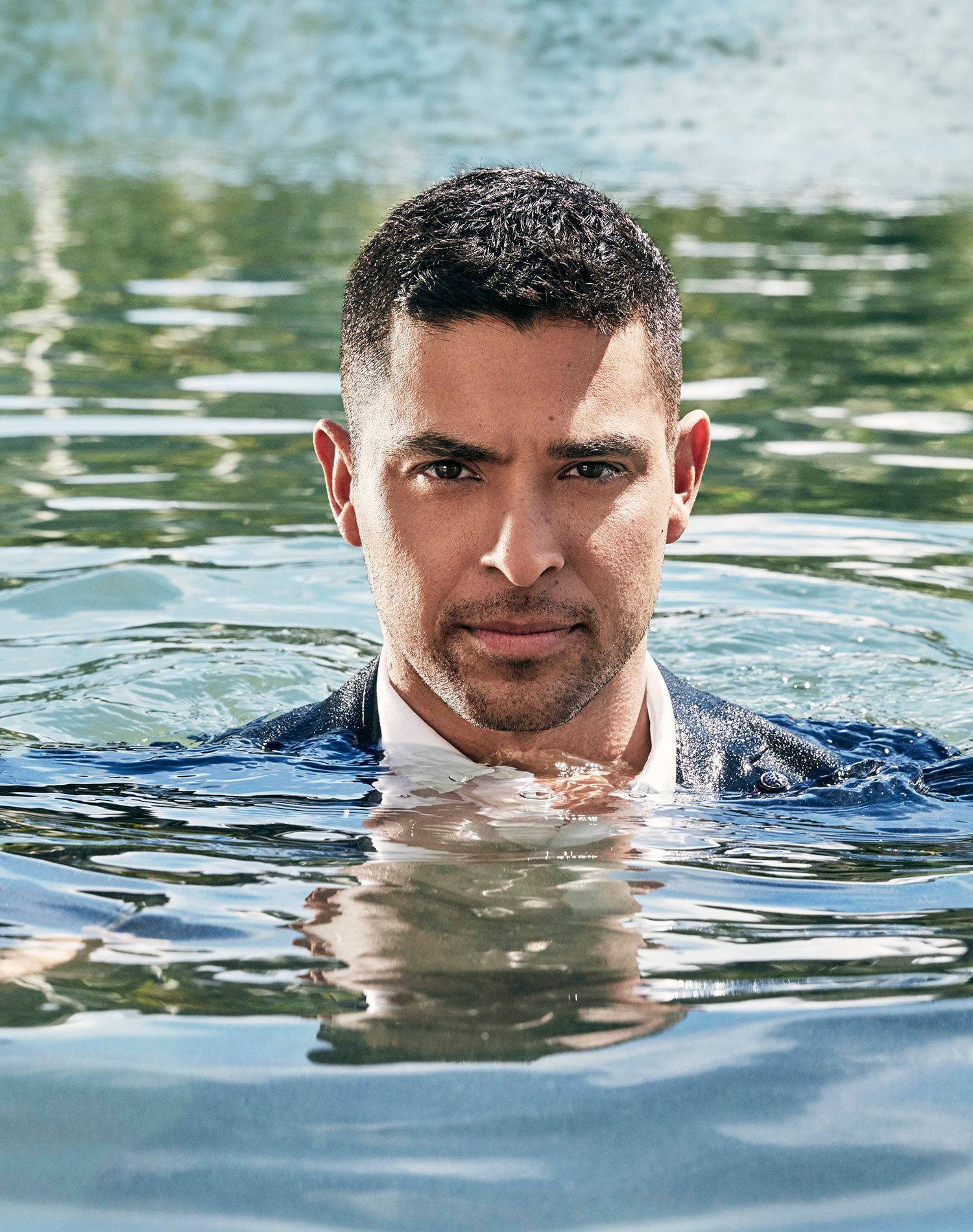 Wilmer Valderrama wearing a suit while in a body of water with just his head above the water