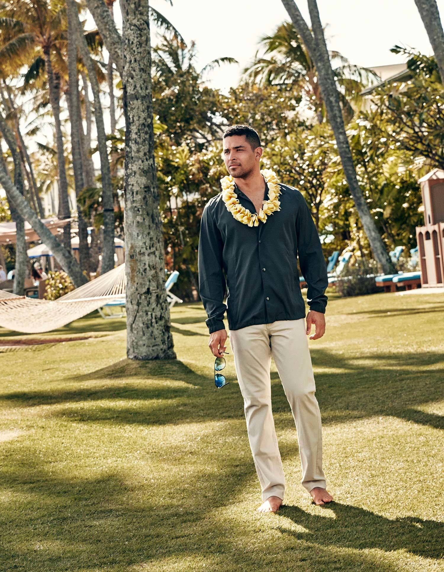 Wilmer Valderrama barefoot on the grass wearing a yellow lei and a green button down shirt