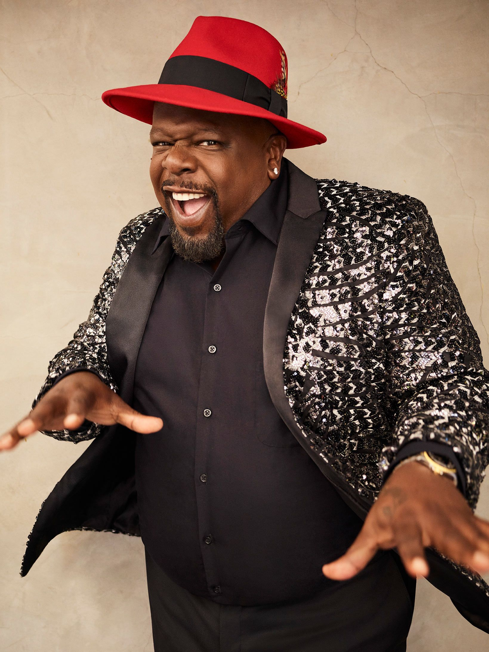 Cedric the Entertainer smiling and wearing a glittery sportscoat.