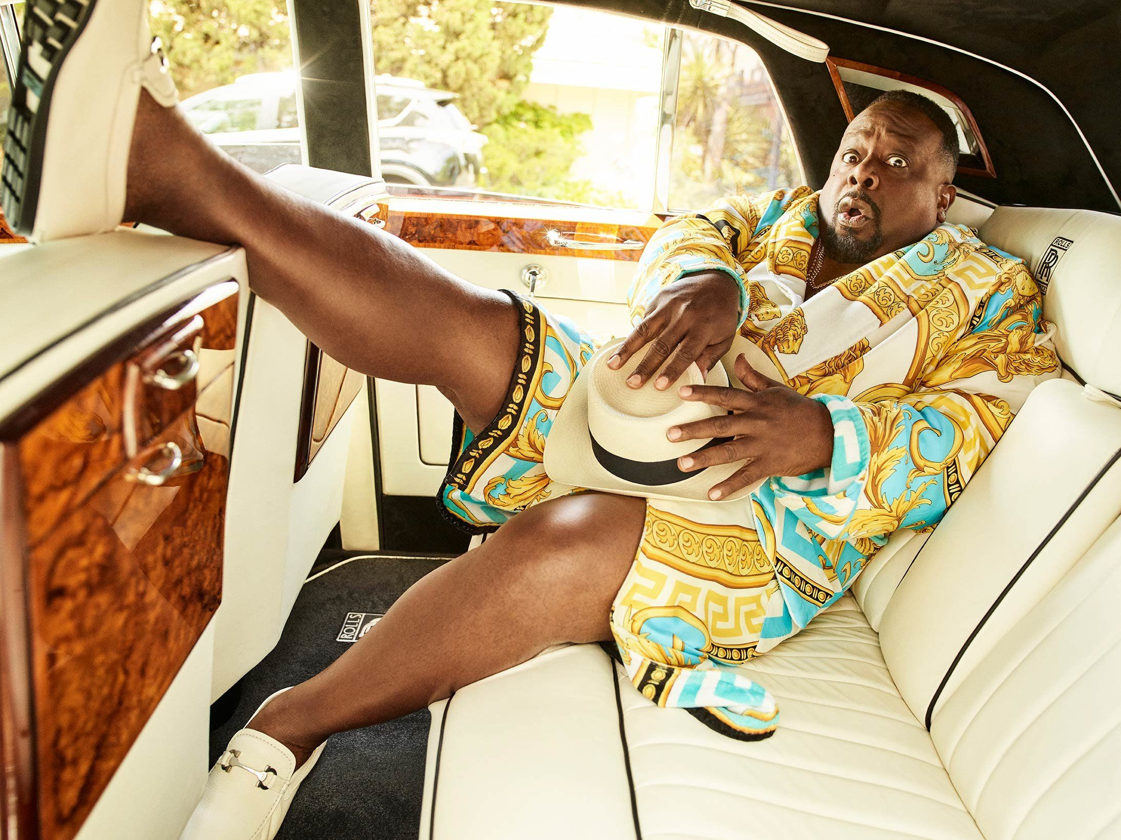 Cedric the Entertainer in silk robe in the back of a Rolls Royce.