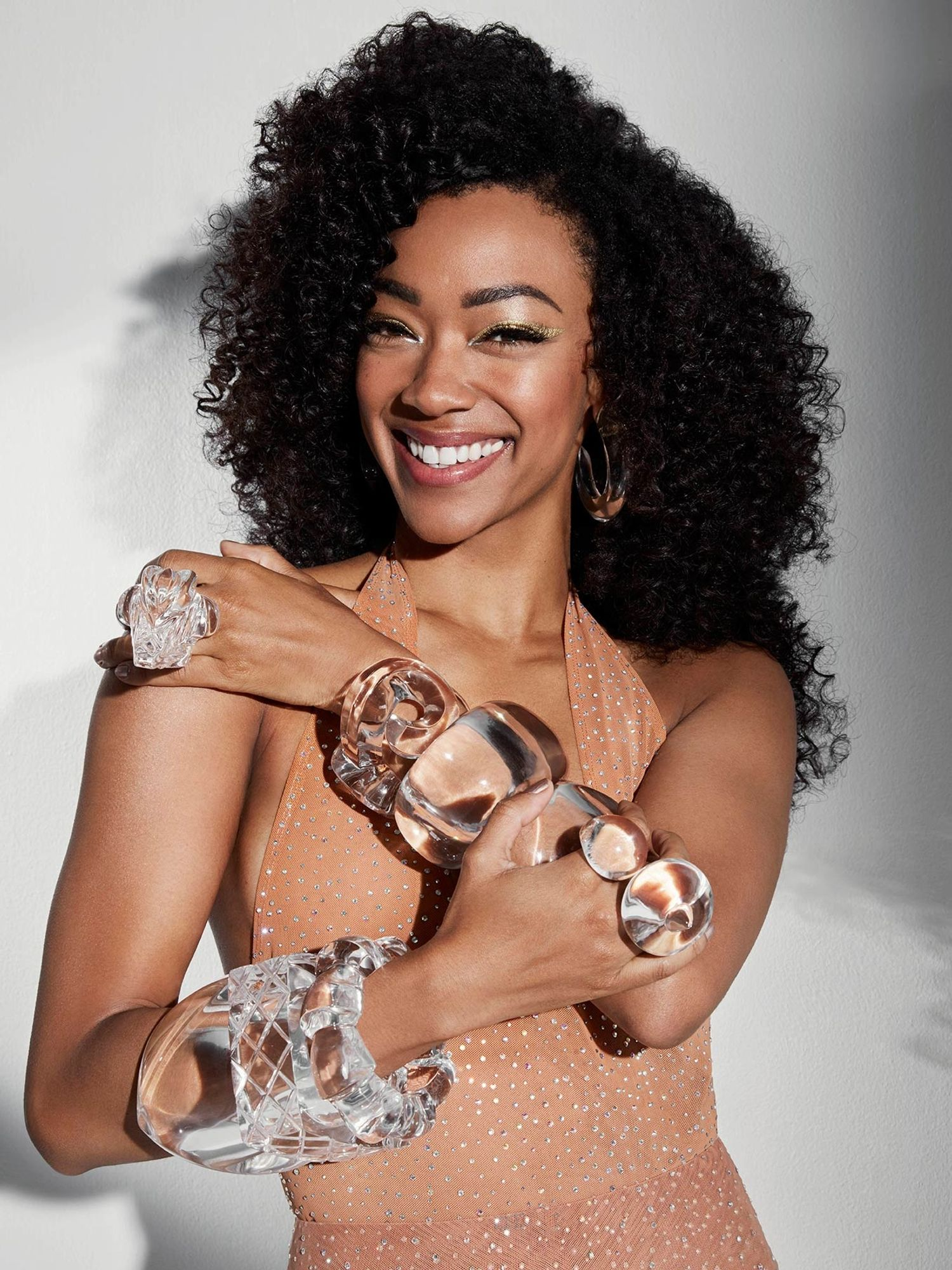 Sonequa Martin-Green smiling wearing lots of clear baubles.