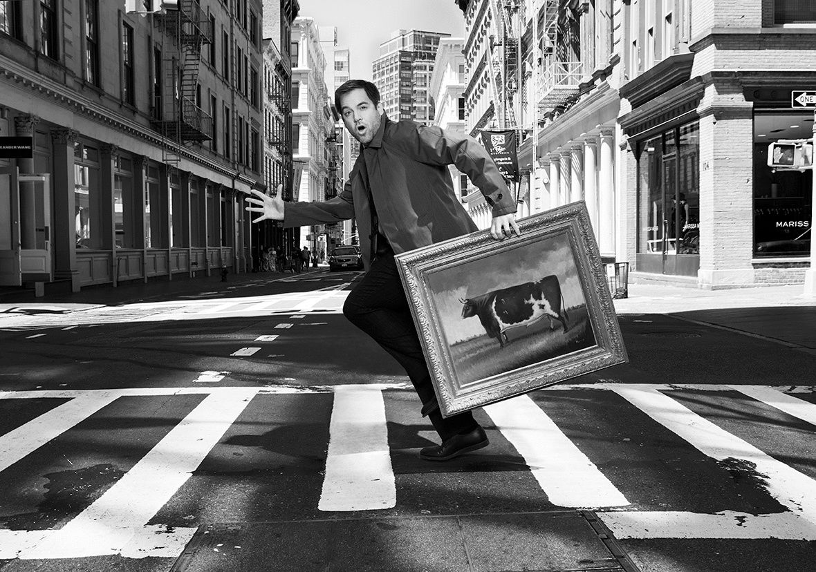 Michael Weatherly in a crosswalk holding a painting of a cow.
