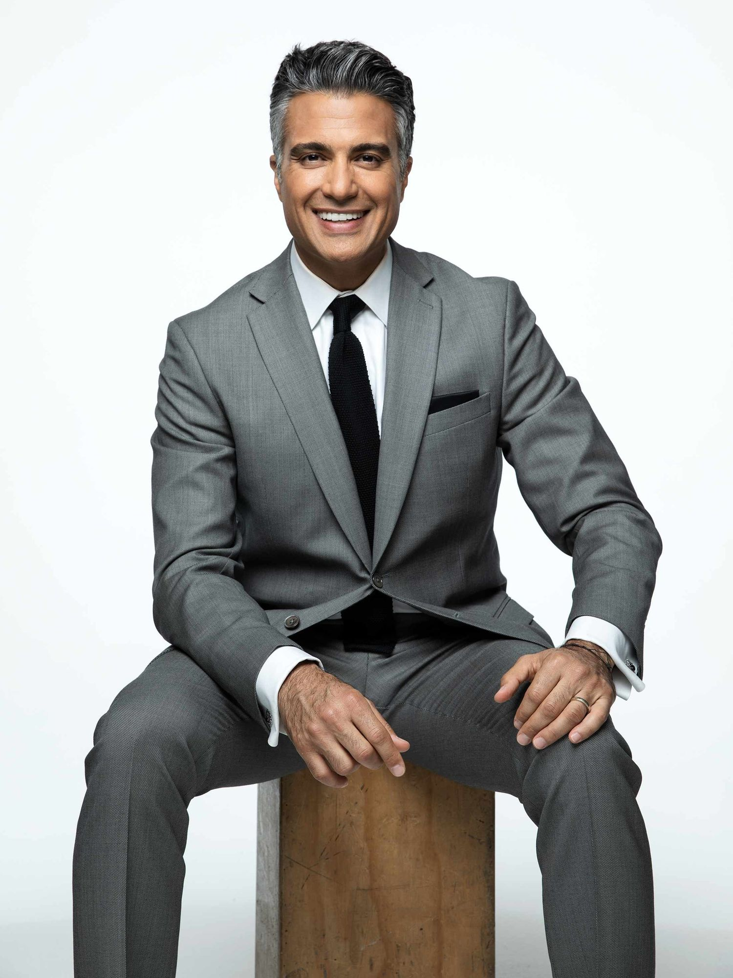Actor Jaime Camil wearing a suit and sitting on a stool.