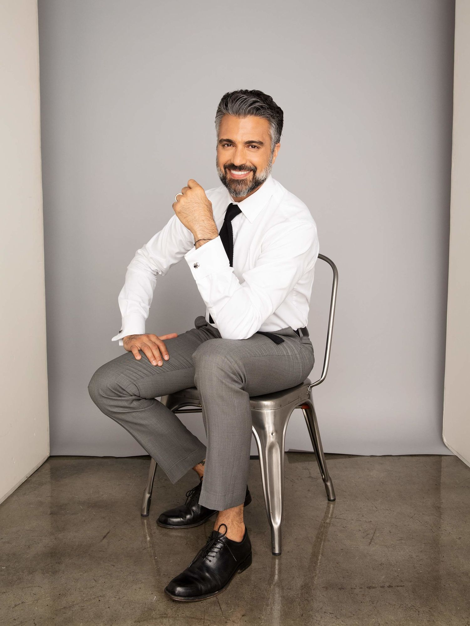 Actor Jaime Camil sitting on a sitting chair and smiling.