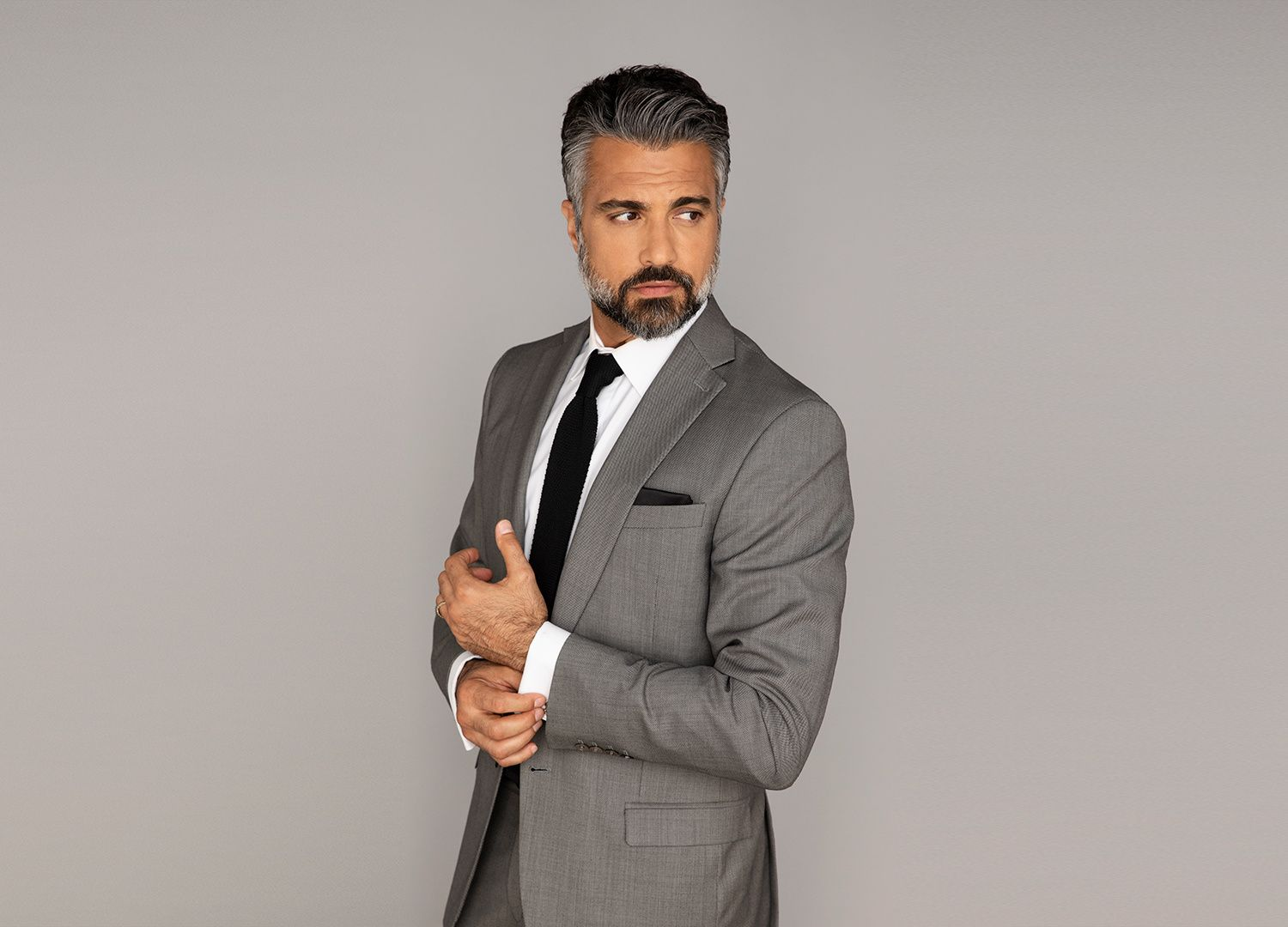 Actor Jaime Camil in a gray suit.