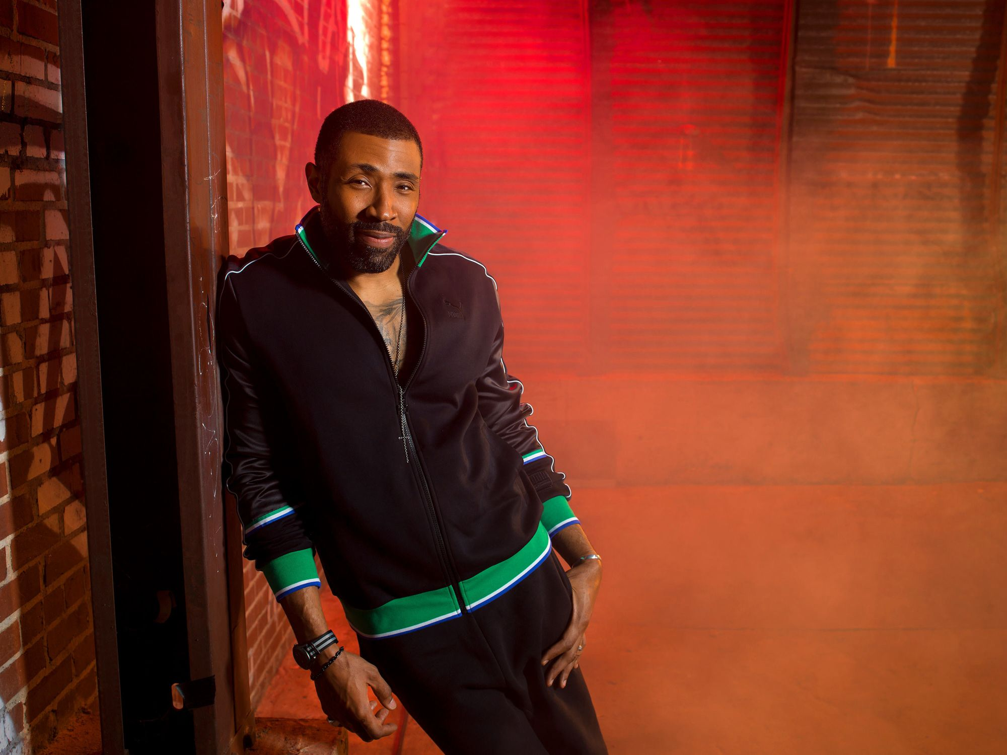 Actor Cress Williams leaning against a wall.