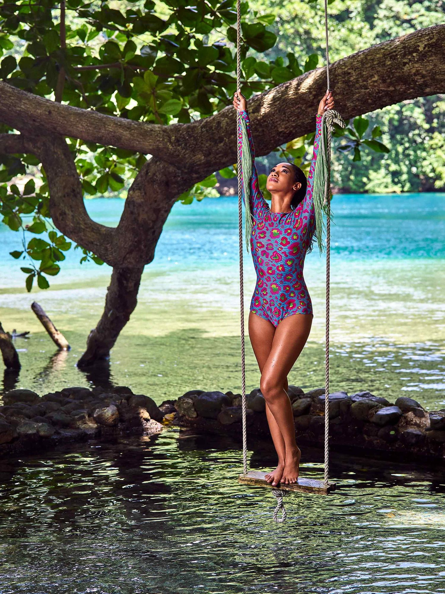 Candice Patton on a swing above a small lagoon.