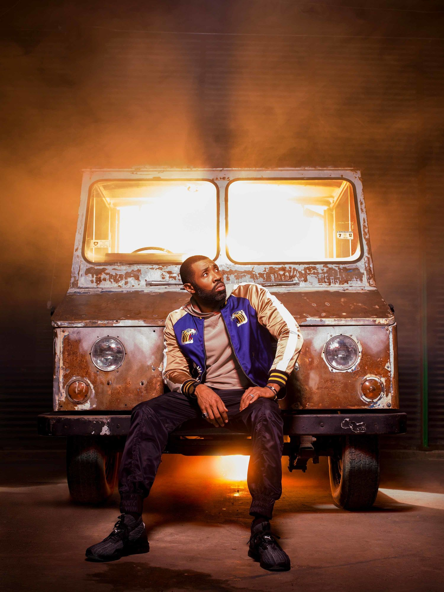 Cress Williams sitting on the front of a rusted truck.