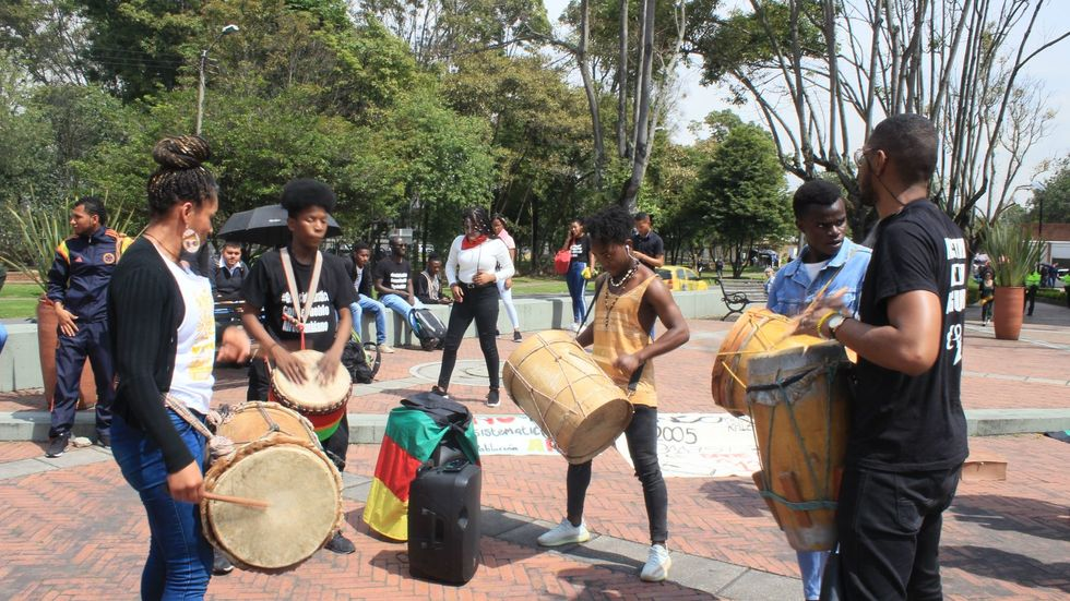 Afro-Colombian, Black, Raizal, and Palenquero civil-rights activists playing drums in front of the census bureau.