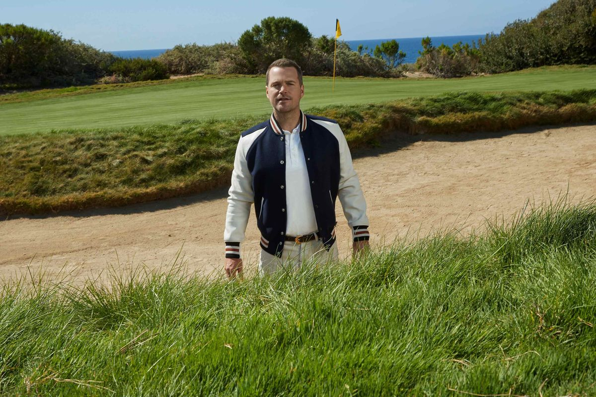 Chris ODonnell in a bomber jacket standing on a gold course