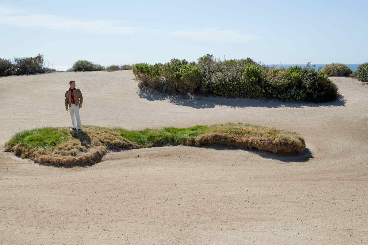 Chris ODonnell standing on a grassy hill surrounded by sand on a gold course