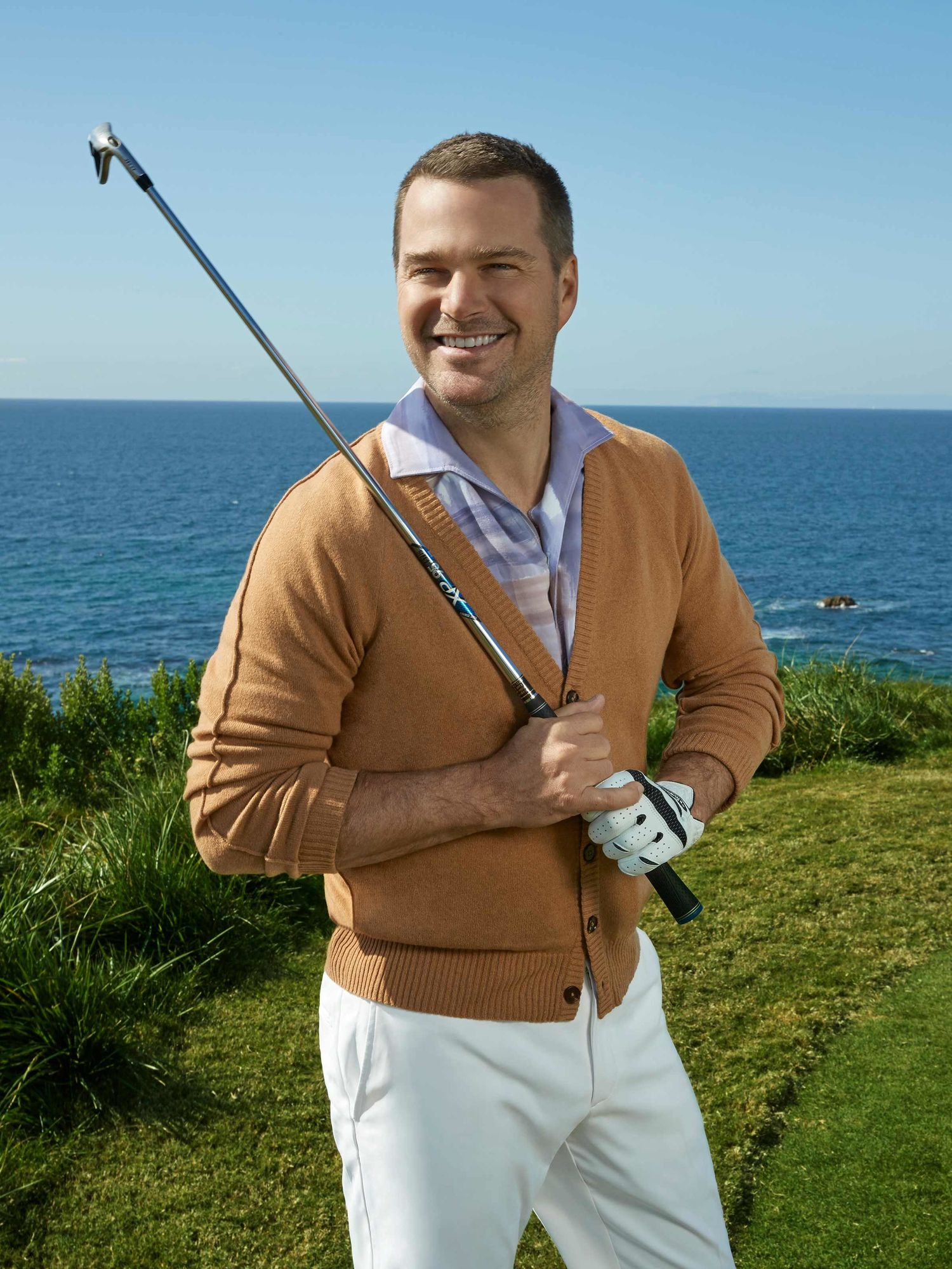 Chris O'Donnell holding a golf club and standing in front of the ocean