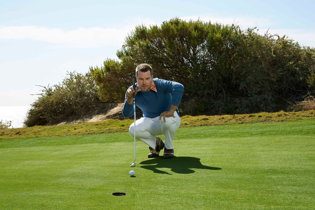 Chris O'Donnell squatting near a hole on a golf course