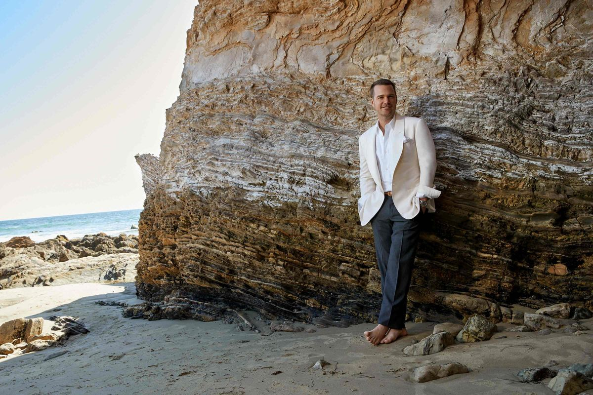 Chris O'Donnell barefoot in the sand wearing a white jacket and gray pants at the base of a cliff