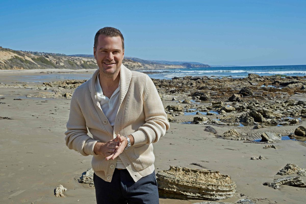Chris O'Donnell wearing a cream cardigan and walking on the beach