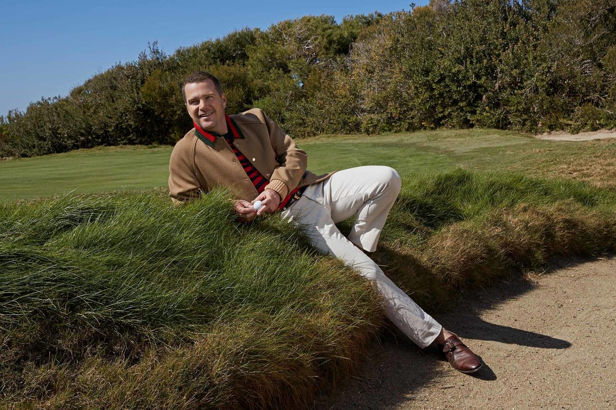 Chris O'Donnell laying in the grass while wearing a camel jacket and white pants