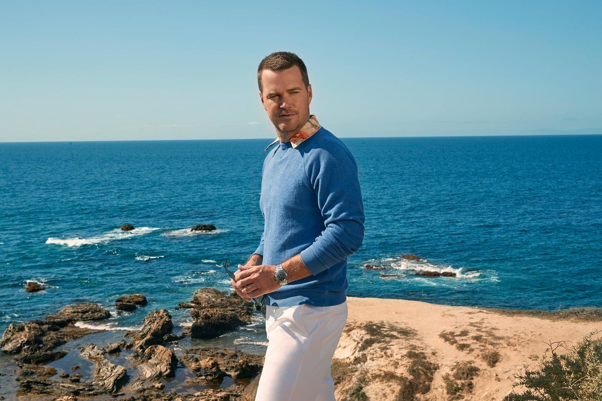 Chris O'Donnell in a blue sweater and white pants in front of the ocean