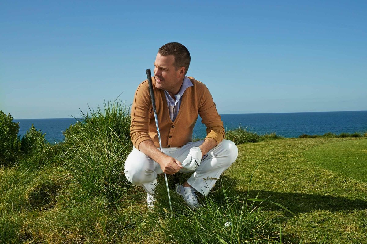 Chris O'Donnell squatting in the grass with a golf club leaning on his shoulder