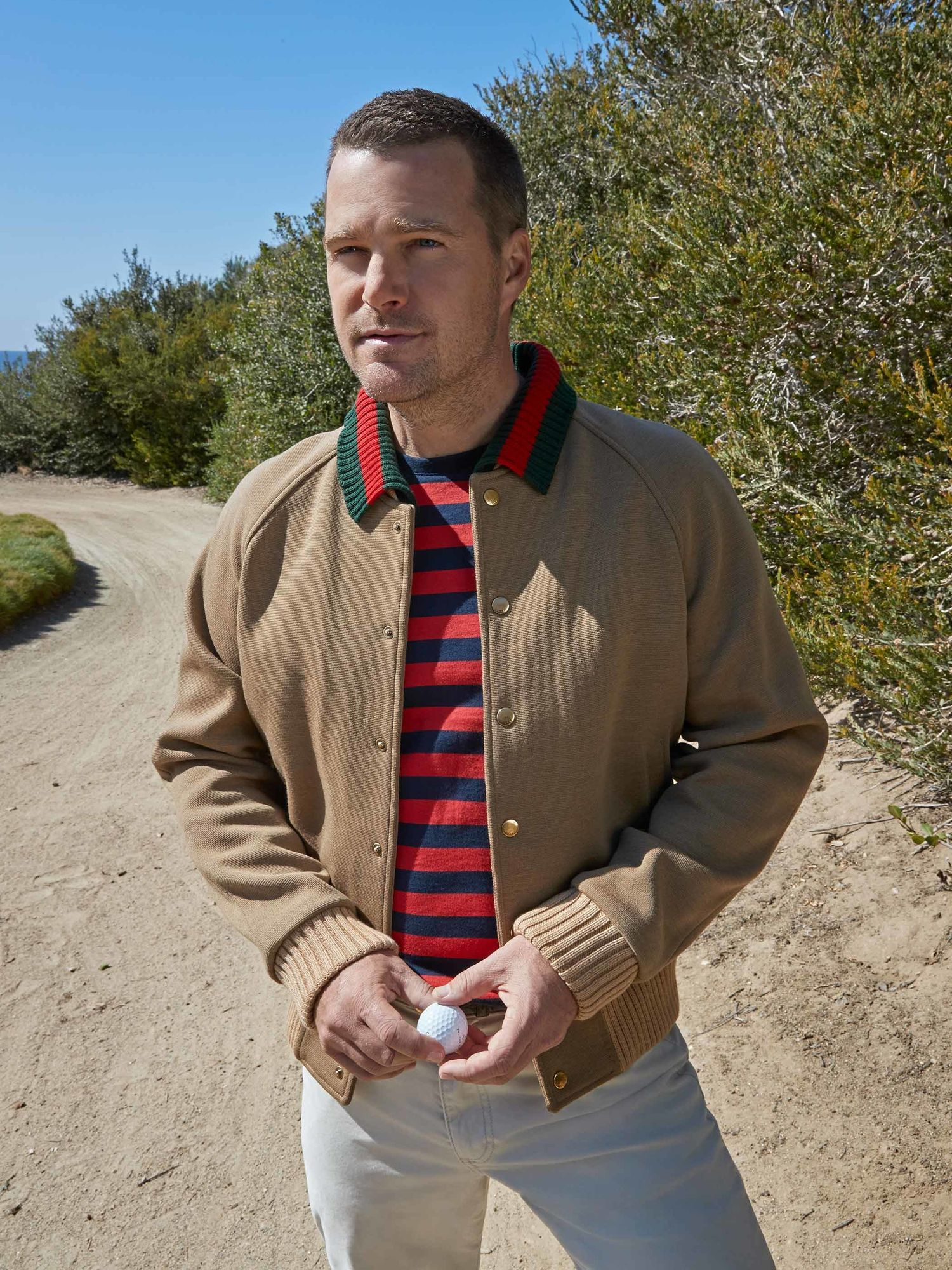 Chris ODonnell in a red and blue striped shirt and camel jacket staring off into the distance