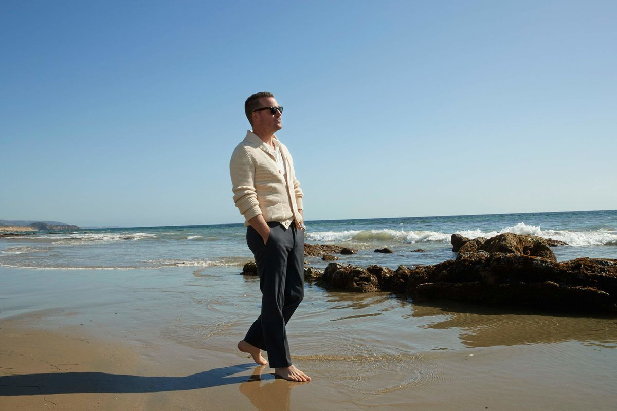 Barefoot Chris O'Donnell walking along the beach in a cream cardigan and gray pants