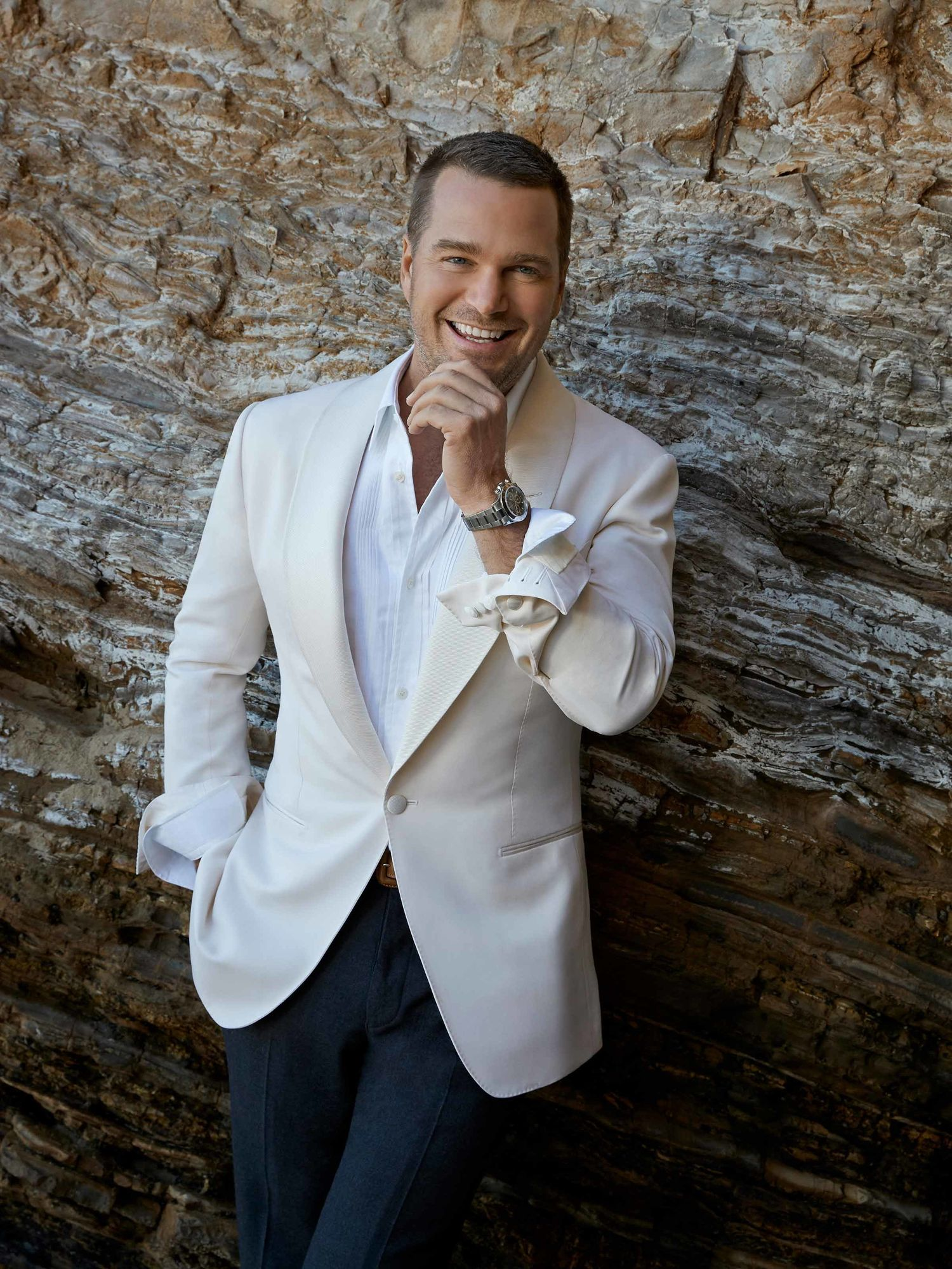 Chris O'Donnell in a cream jacket and white shirt and smiling with his hand on his chin