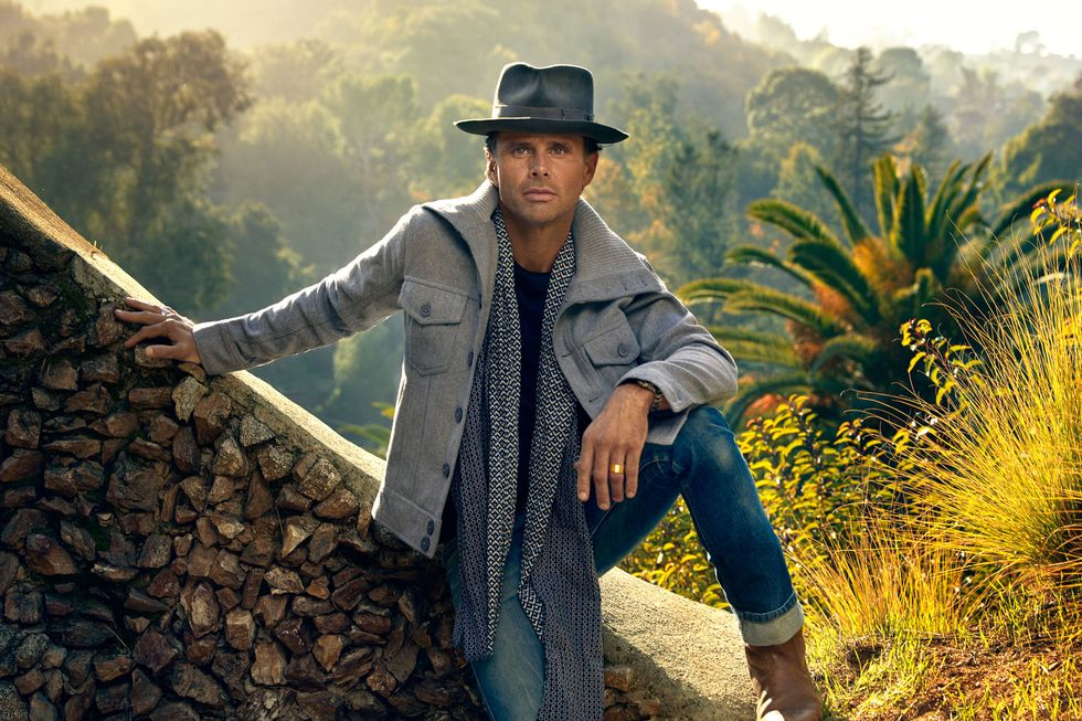 Walton Goggins sitting on a stone wall staring into the camera.