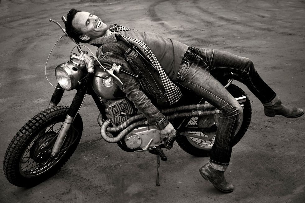 Black and white image of Walton Goggins reclining on a vintage motor cycle.