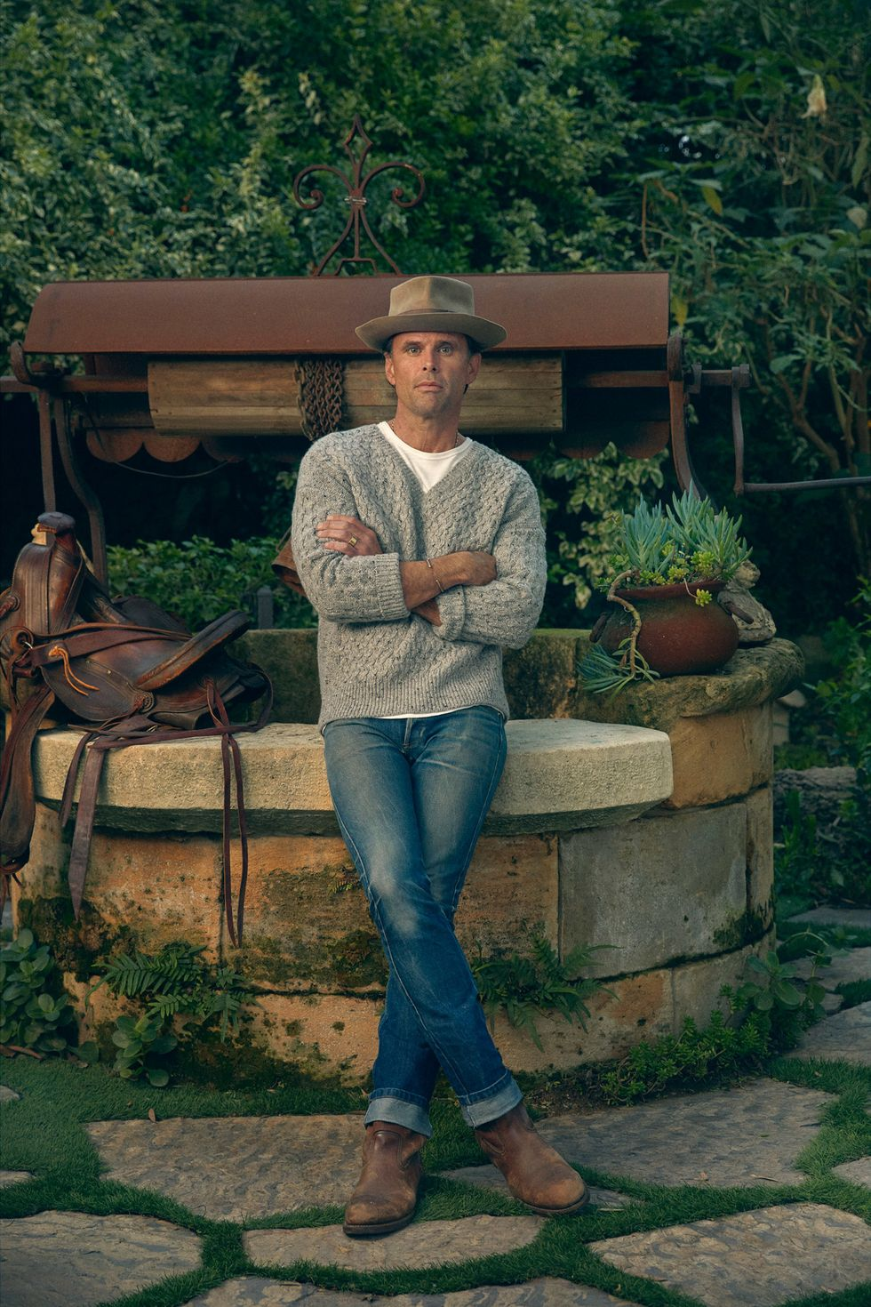 Walton Goggins leaning against the edge of a water well with a saddle beside him.