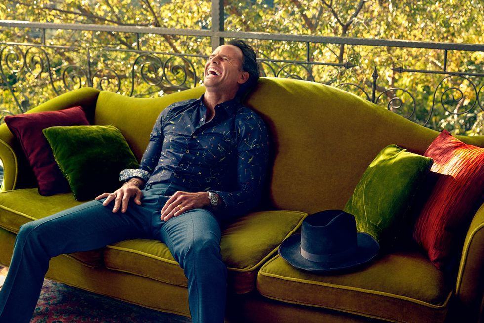 Walton Goggins lounging and laughing on a mustard color velvet sofa.