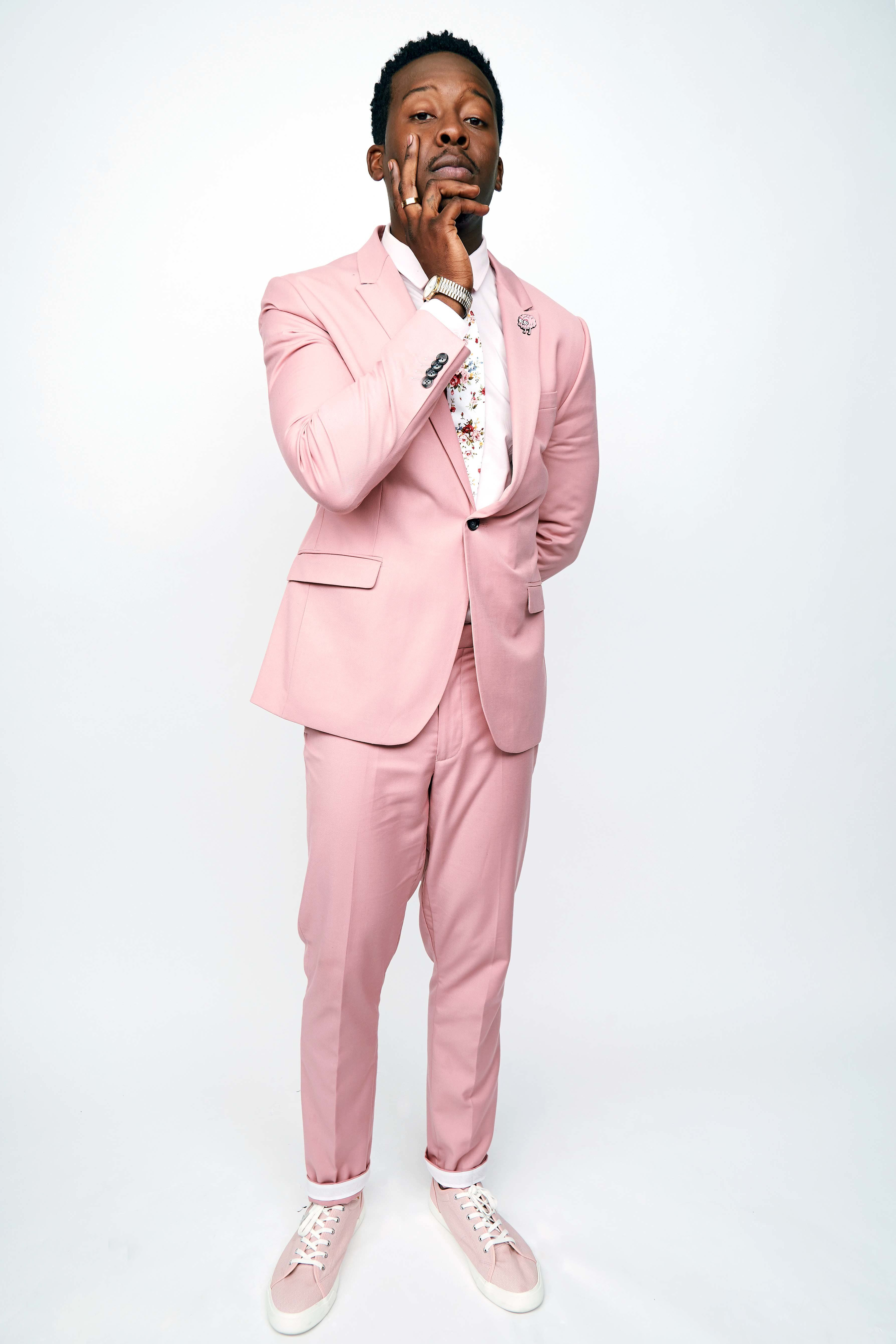 Actor Brandon Micheal Hall in a pink suit.
