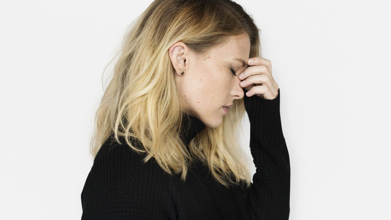 woman wearing black sweater on white background thinking concept of being stressed and anxious