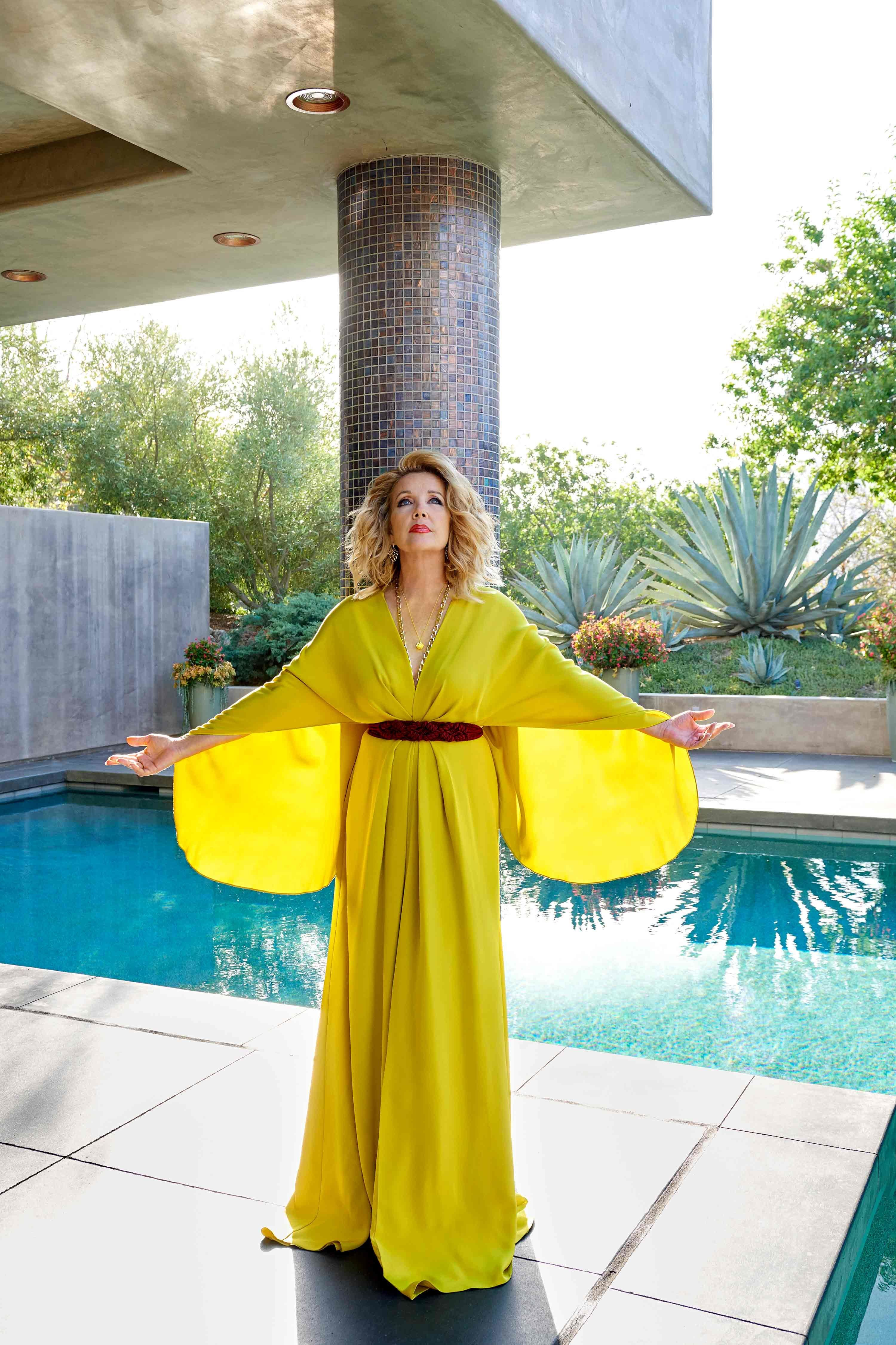 Melody Thomas Scott of The Young and the Restless in a cape style gold McQueen gown