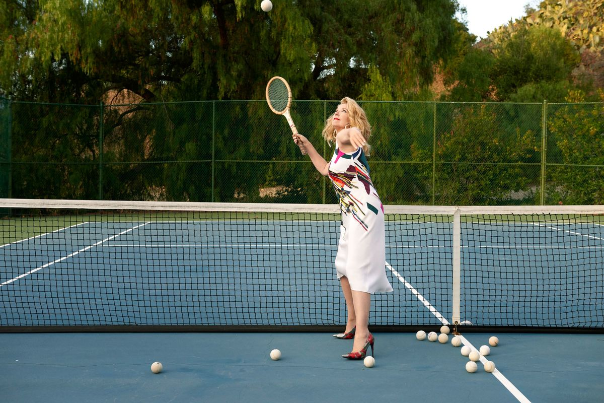 Melody Thomas Scott serving on a tennis court in high heels
