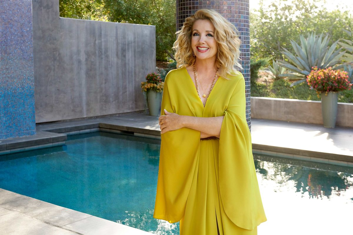 Melody Thomas Scott of The Young and the Restless in a gold gown next to a swimming pool
