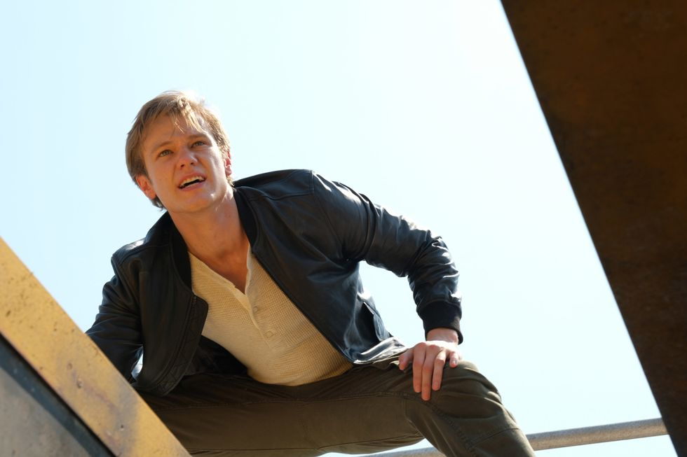 Actor Lucas Till looking down from a roof.