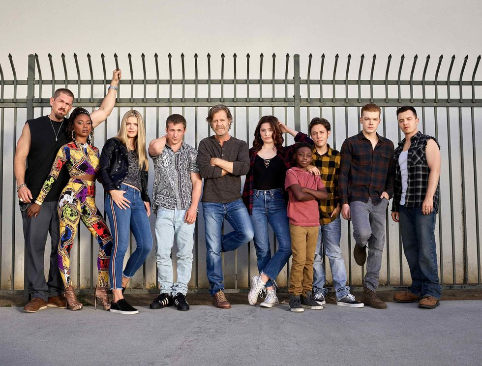 The cast of Shameless leaning against a metal fence.