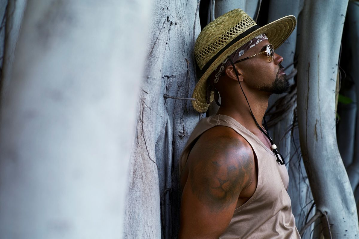 Shemar Moore wearing a wide-brimmed hat and tan tank top in front of some mangrove trees
