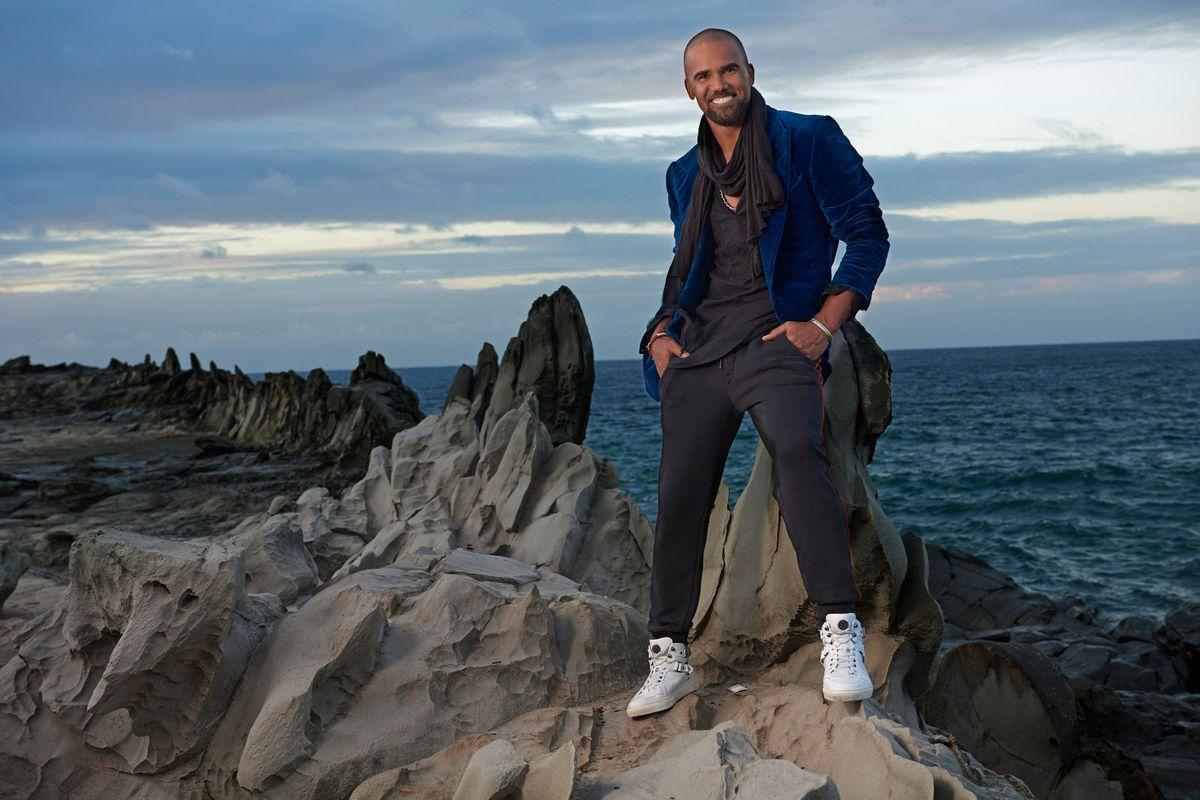 Shemar Moore standing on rocky terrain by the ocean in a velvet blue jacket