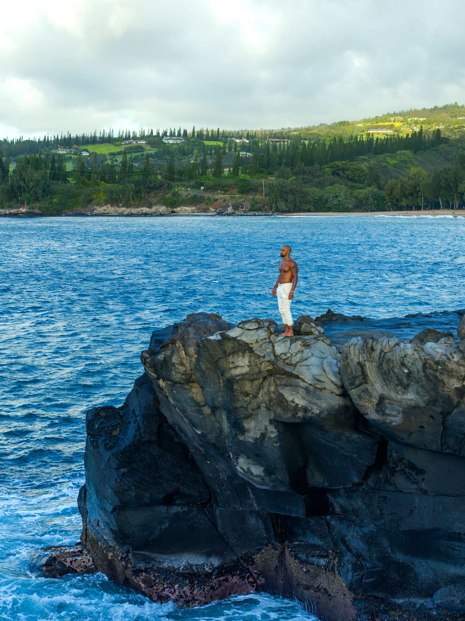 Shemar Moore standing on rocky terrain by the ocean with his shirt off and in white pants