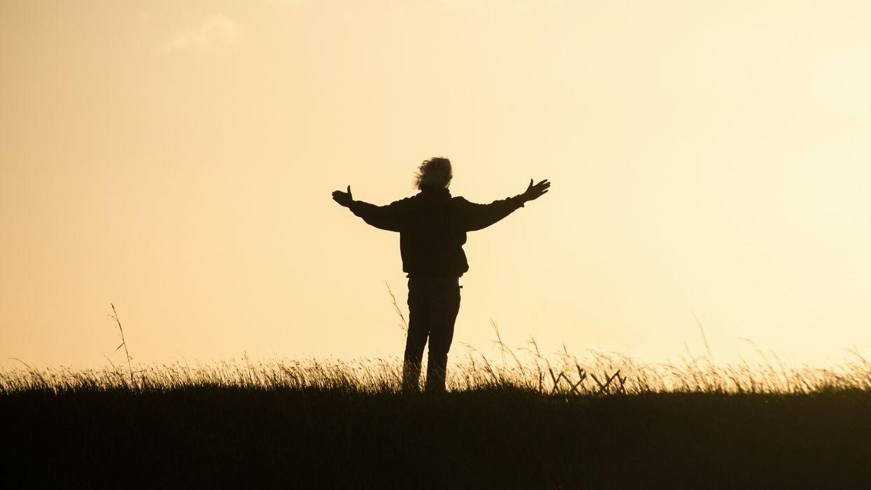 personal standing on hill at sunset with arms outstretched