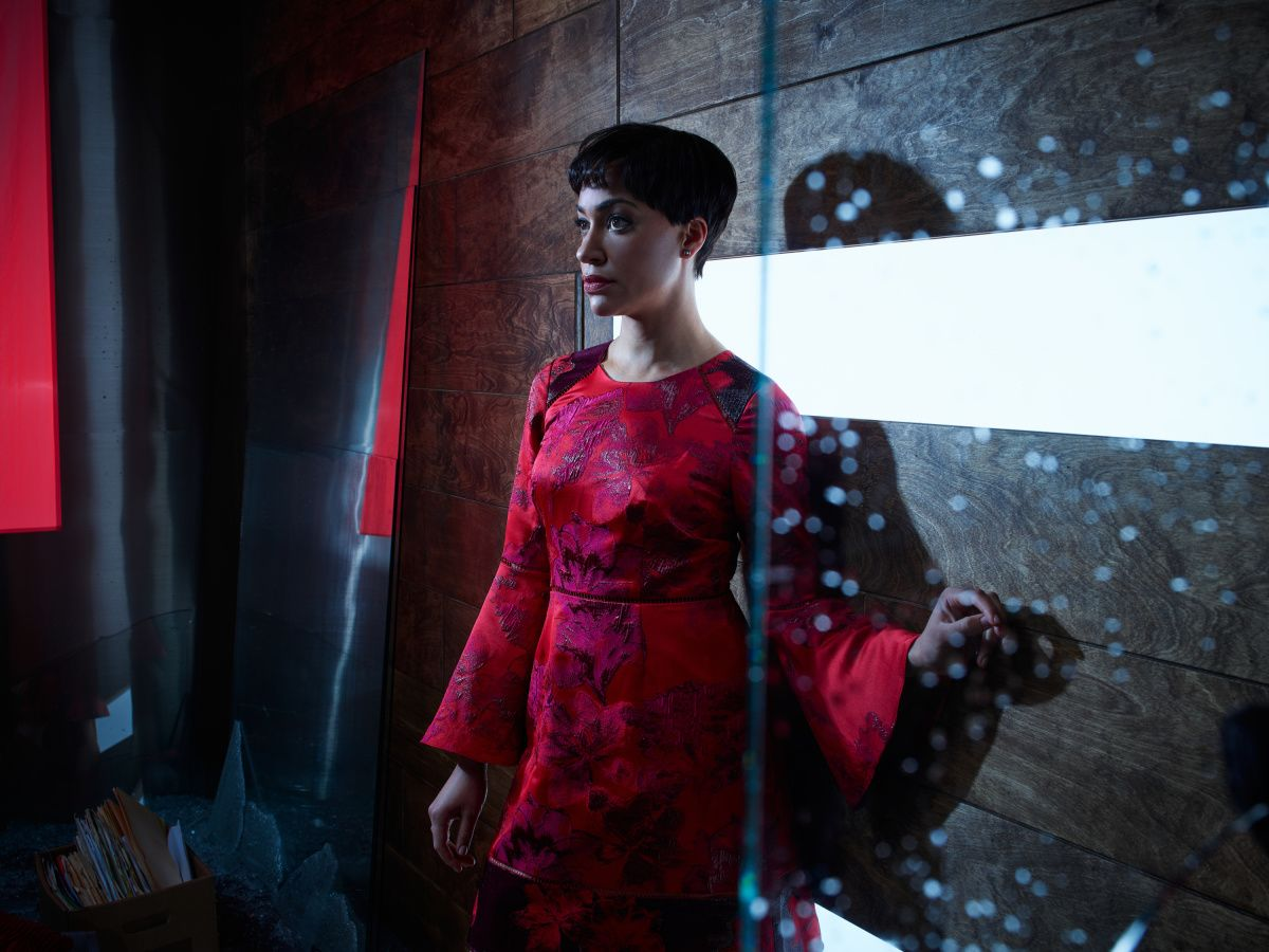 Actress Cush Jumbo leaning against a wall in red dress.