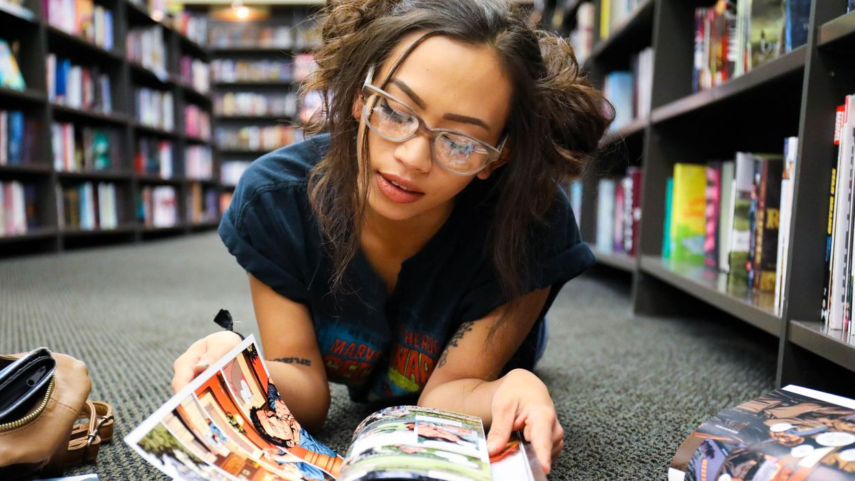 young woman reading graphic novels on the floor