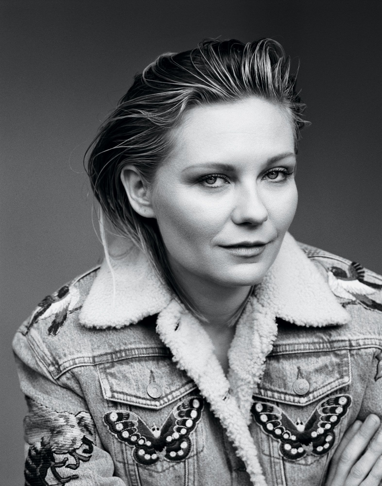 Black and white portrait of Kirsten Dunst in denim jacket.