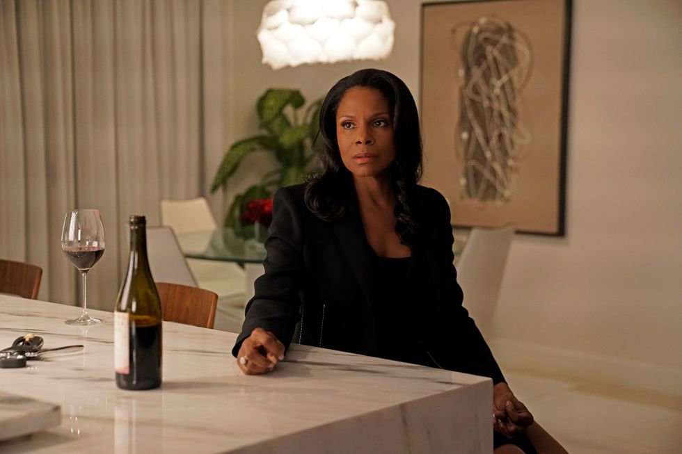 Audra McDonald as Liz Reddick-Lawrence sitting at a table with a wine bottle and full glass