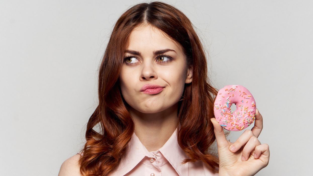 bored woman holding pink donut concept of emotional eating