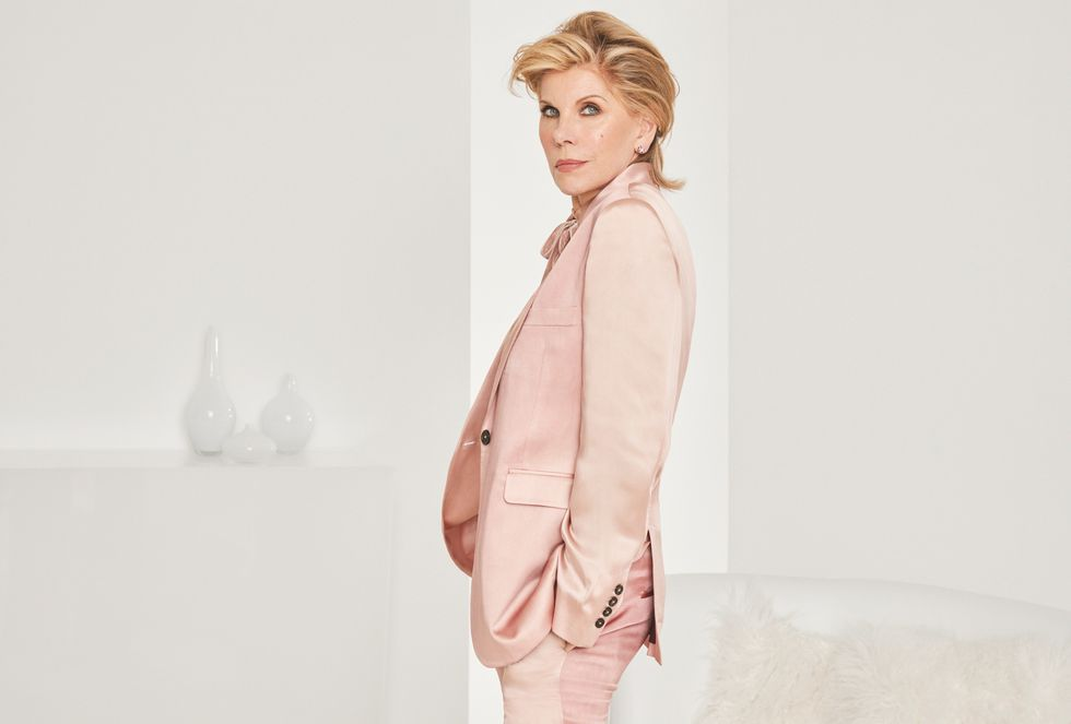 Christine Baranski a power pose in a pink suit.