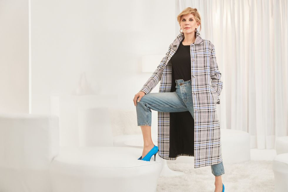 Christine Baranski in a plaid coat, cropped jeans, and bright blue high heels.