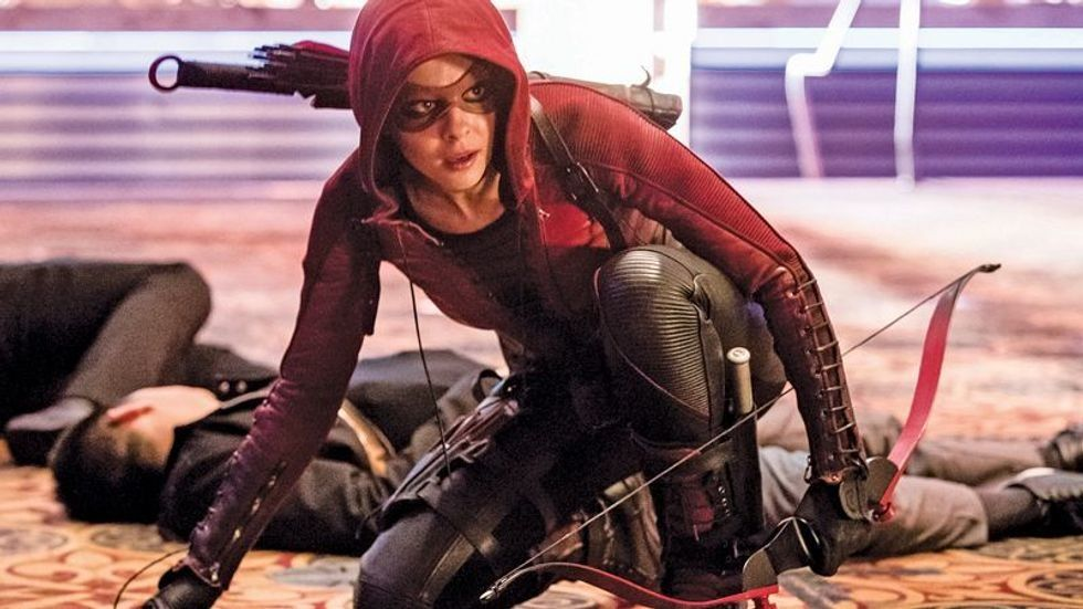 Willa Holland as Thea Queen in Arrow bending down with a bow in her hand